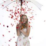 Meisje in witte jurk onder paraplu met rode rozen